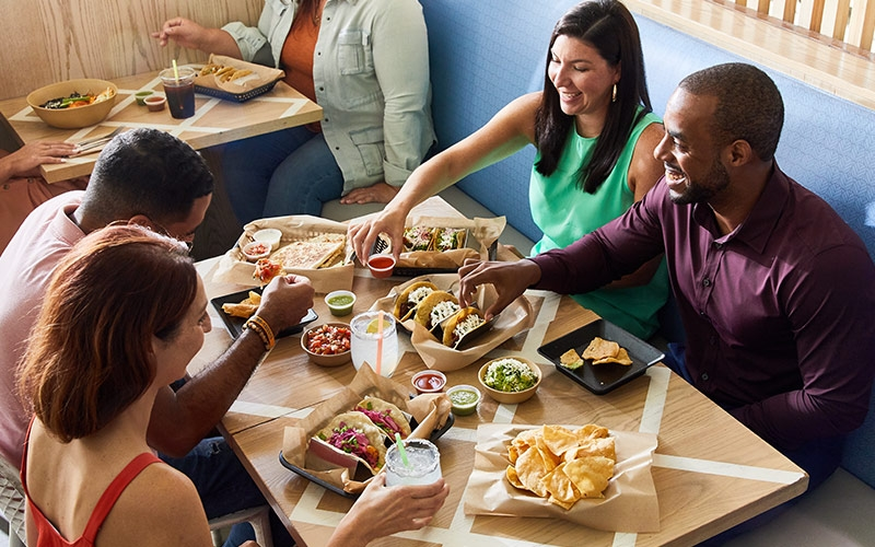 Diners seated at table sharing tacos, chips, and salsa