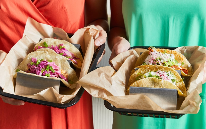 Two ladies holding Baja Style Buena Onda tacos standing next to each other