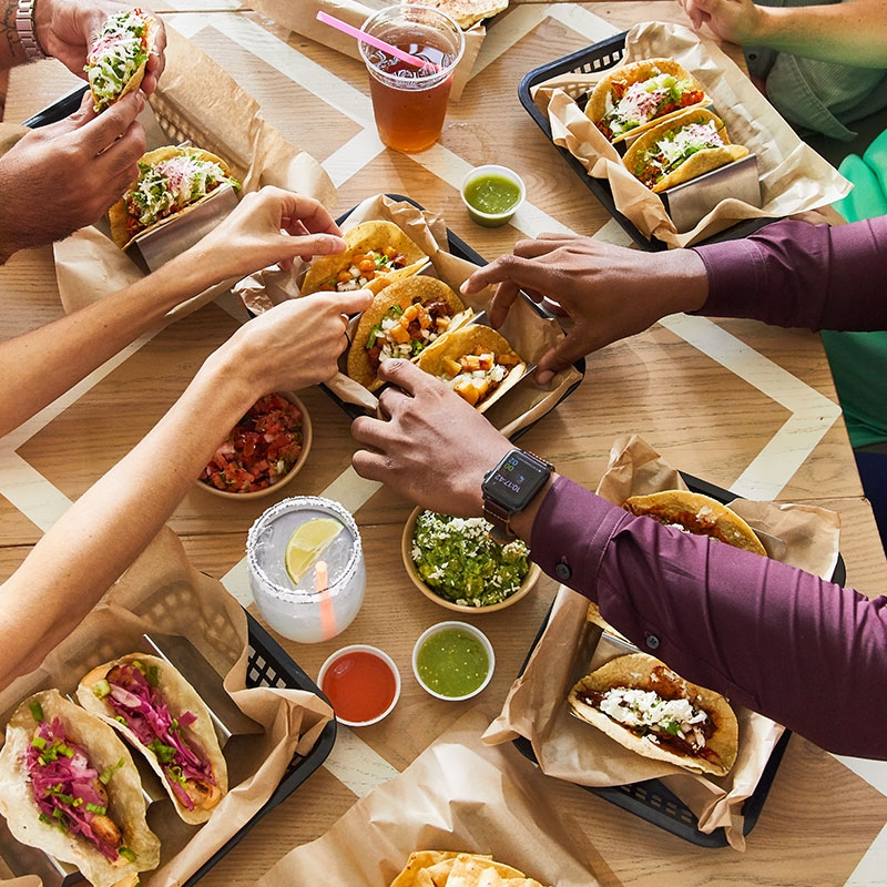 Guests around a table of Buena Onda tacos fixing a plate at party