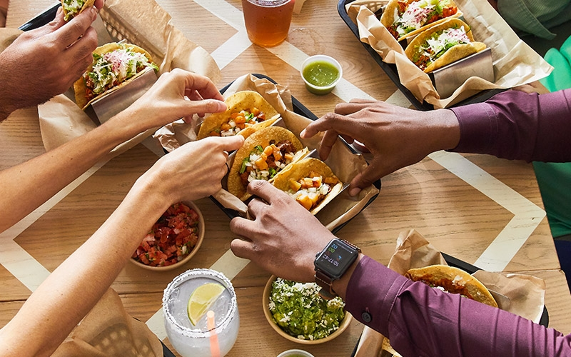 Table of food with multiple hands shown grabbing a taco